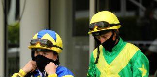 Masked jockeys following the return of racing.