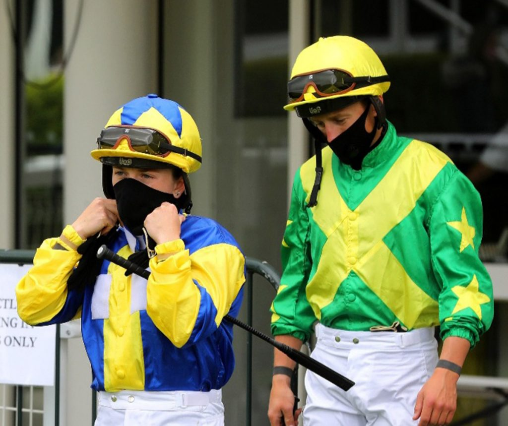 Masked jockeys following the return of racing.